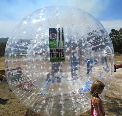 A girl walking in front of a zorb ball with Denmark Thrills Adventure Park logo on it